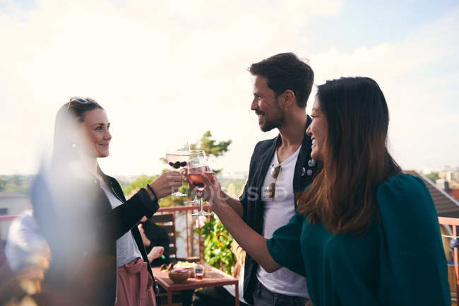 Smiling friends toasting drinks while partying on terrace — Stock Photo