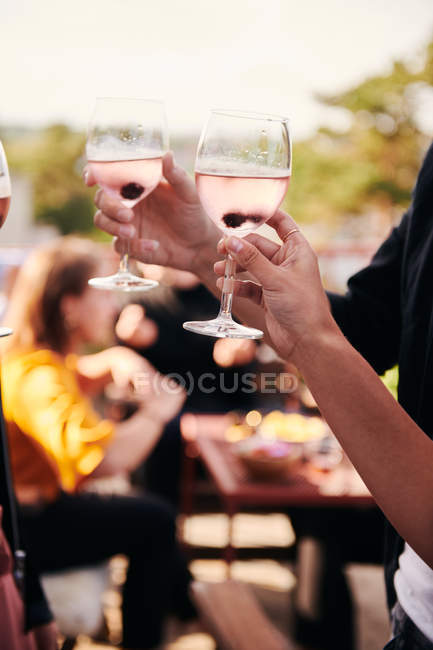 Cropped hands of friends holding wineglasses during social gathering on terrace — Stock Photo