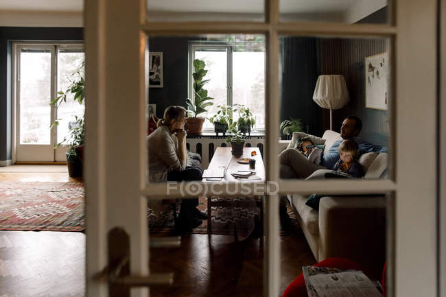 Family using various technologies in living room seen through transparent door at home — Stock Photo