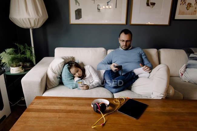Padre e figlia utilizzando i telefoni cellulari sul divano in soggiorno a casa — Foto stock