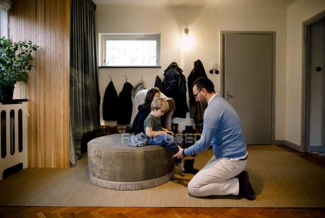 Vater hilft Tochter beim Tragen von Schuhen zu Hause — Stockfoto