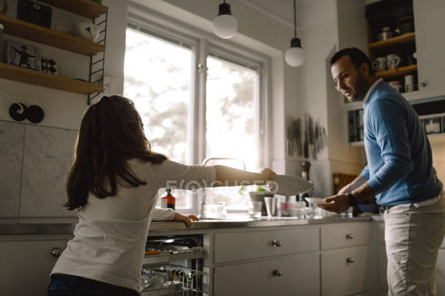 Daughter giving plate to father while standing in kitchen at home — Stock Photo