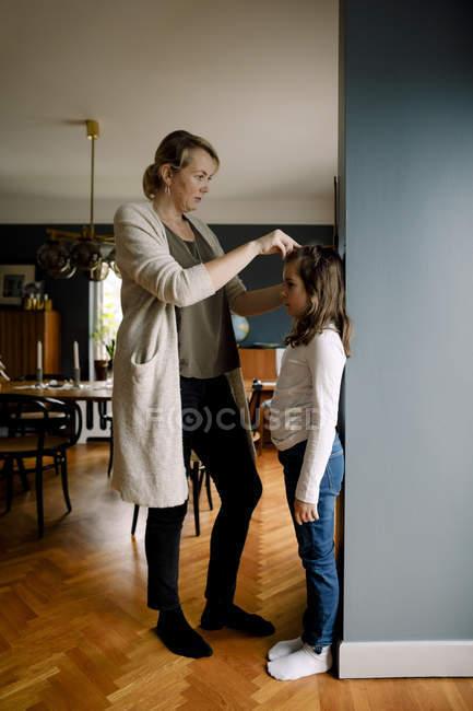 Longitud completa de la madre midiendo la altura de la hija contra la pared en casa - foto de stock