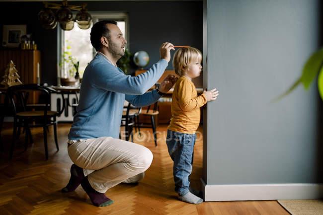 Longitud completa del padre midiendo la altura de la hija contra la pared en casa - foto de stock