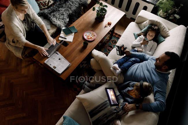 Высокоугольный вид на семью с использованием различных технологий в гостиной дома — стоковое фото