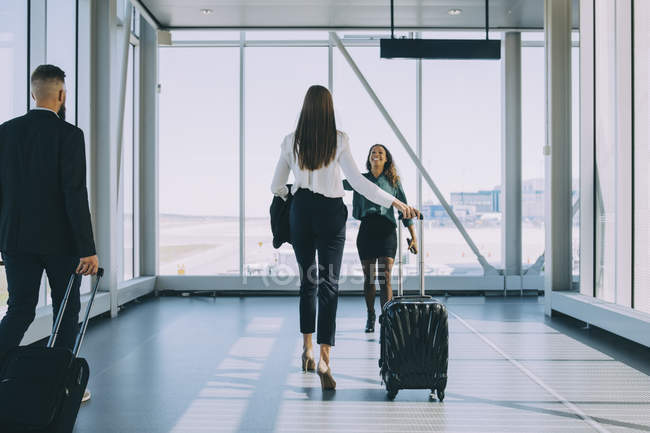 Smiling businesswoman walking towards female colleague in corridor at airport — Stock Photo