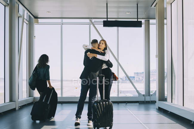 Businesswoman walking by colleagues greeting in corridor at airport — Stock Photo