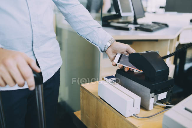 Midsection of businessman scanning ticket on smart phone at airport check-in counter — Stock Photo