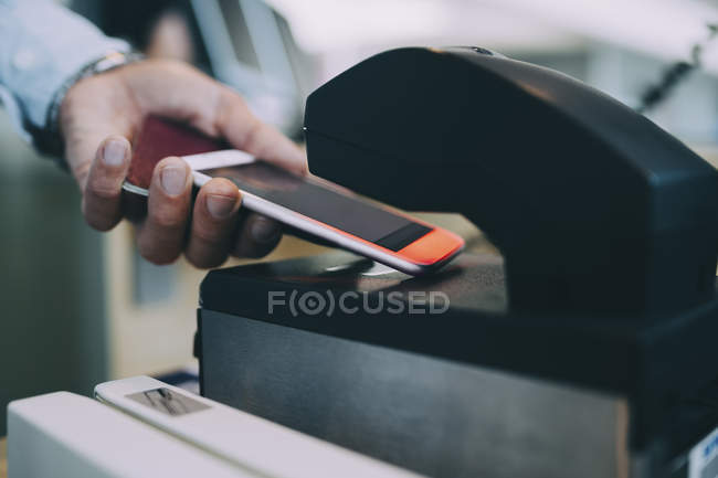 Mãos cortadas do bilhete da exploração do homem de negócios no telefone esperto no contador do check-in do Aeroporto — Fotografia de Stock