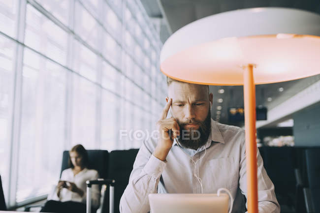 Homme d'affaires regardant la vidéo sur la tablette numérique tout en s'asseyant à la table dans la zone de départ d'aéroport — Photo de stock