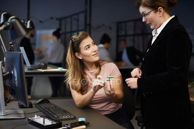 Kreative Geschäftsfrau diskutiert mit Bankmanager über Solar-Spielzeugauto im Kreativbüro — Stockfoto