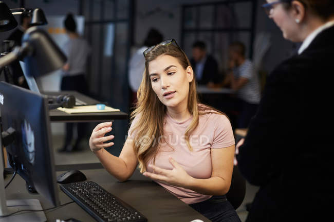 Kreative Geschäftsfrau erklärt Bankmanagerin am Schreibtisch im Kreativbüro — Stockfoto