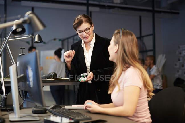 Kreative Geschäftsfrau betrachtet Bankmanagerin mit solarem Spielzeugauto im kreativen Büro — Stockfoto
