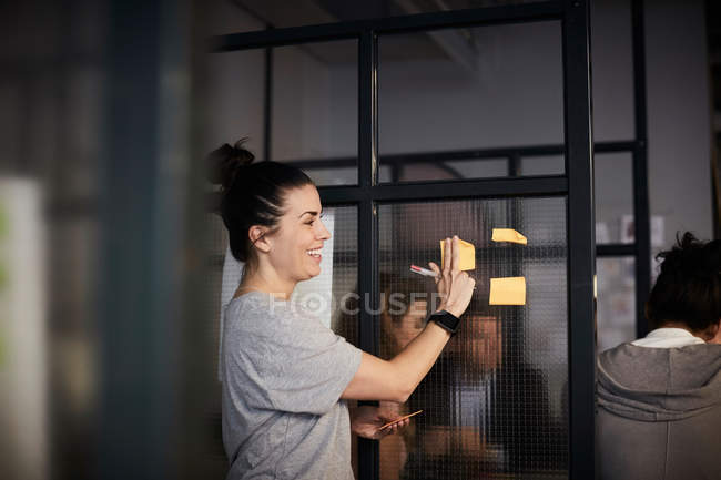 Smiling creative businesswoman sticking adhesive note on glass in office — Stock Photo