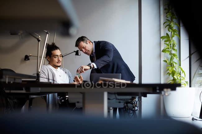 Kreativer Geschäftsmann diskutiert mit Bankmanager über Solar-Spielzeugauto im Kreativbüro — Stockfoto