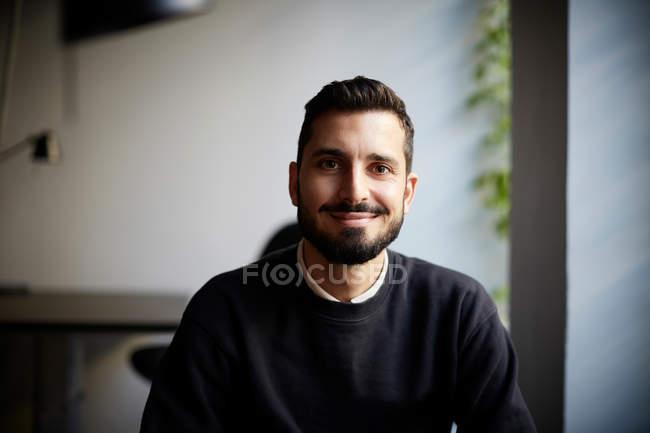 Verticale d'entrepreneur masculin confiant s'asseyant dans le bureau créateur — Photo de stock