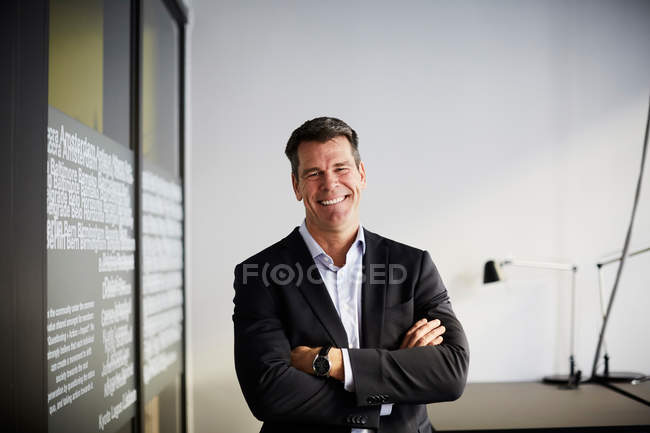 Portrait of confident mature businessman standing with arms crossed in office — Stock Photo