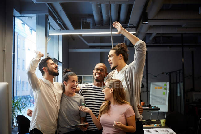 Male and female entrepreneurs cheering in creative office — Stock Photo