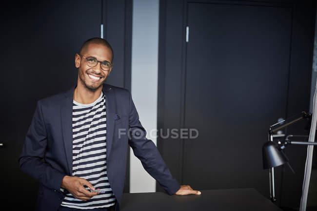 Ritratto di imprenditore uomo fiducioso in piedi in ufficio creativo — Foto stock