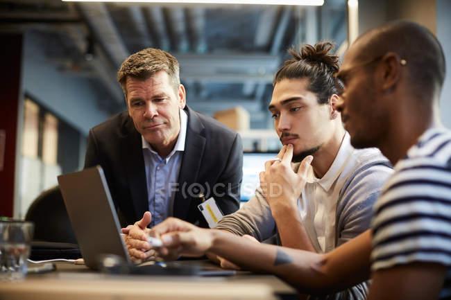 Empresario masculino dando presentación sobre portátil en el escritorio en la oficina creativa - foto de stock