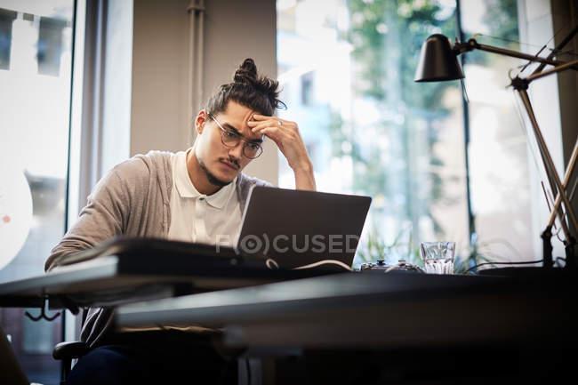 Напряженный бизнесмен, глядя на ноутбук, сидя в творческом офисе — стоковое фото