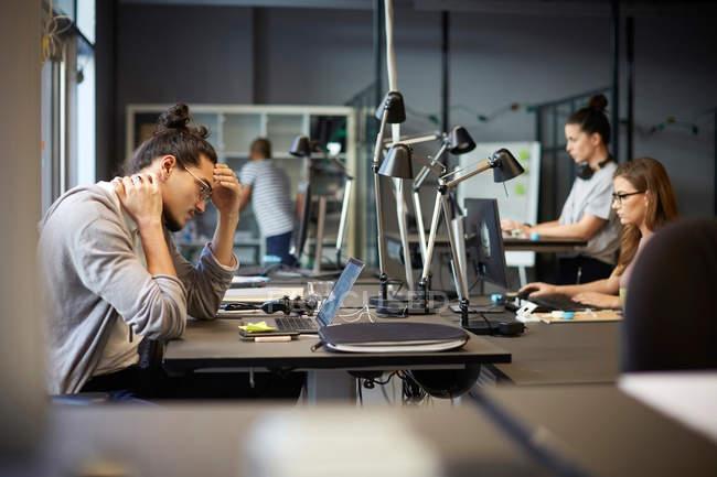 Напряженный мужчина предприниматель, глядя на ноутбук, сидя в творческом офисе — стоковое фото