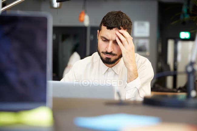 Entrepreneur masculin stressé regardant l'ordinateur portatif tout en s'asseyant dans le bureau — Photo de stock