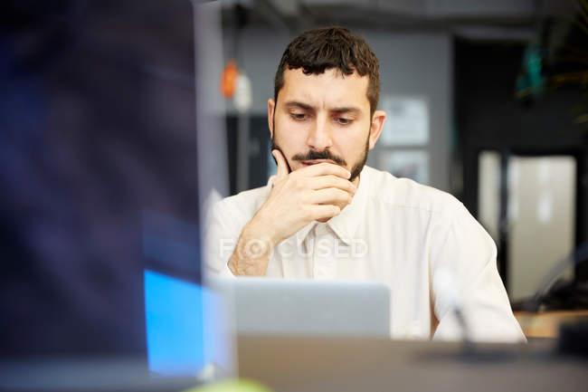 Homme d'affaires créateur stressé regardant l'ordinateur portatif tout en s'asseyant dans le bureau — Photo de stock