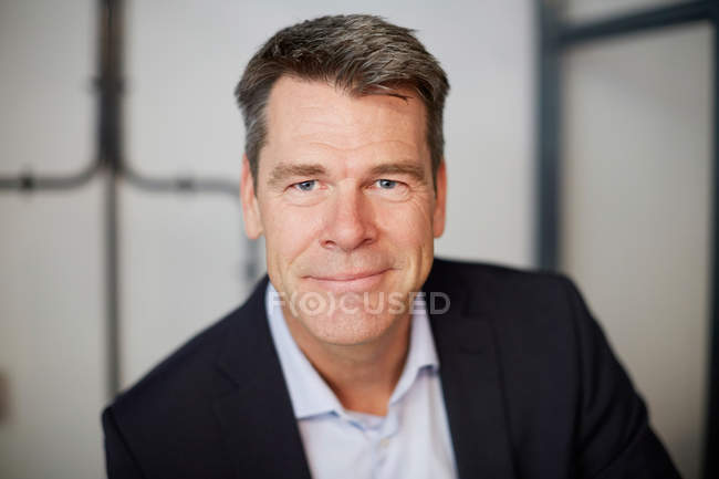 Portrait of confident mature businessman sitting in office — Stock Photo