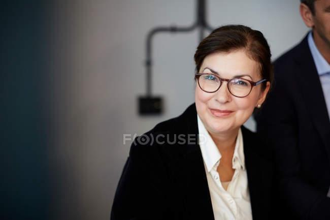 Портрет уверенно зрелой бизнес-леди, сидящей в офисе — стоковое фото