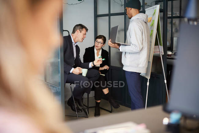 Bankmanager diskutieren über Solar-Spielzeugauto, während Geschäftsmann Vortrag im Kreativbüro hält — Stockfoto