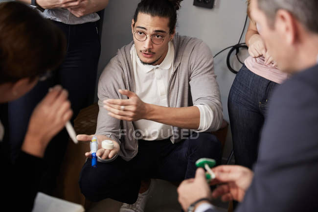 Male entrepreneur explaining project to bank managers during meeting in creative office — Stock Photo
