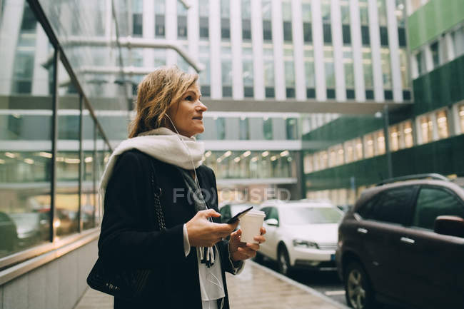 Femme d'affaires avec café et téléphone intelligent regardant loin tout en se tenant sur le trottoir contre le bâtiment moderne dans la ville — Photo de stock