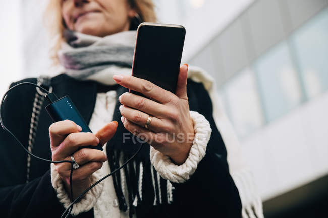 Midsection of businesswoman holding mobile phone with charger while standing against building in city — Stock Photo