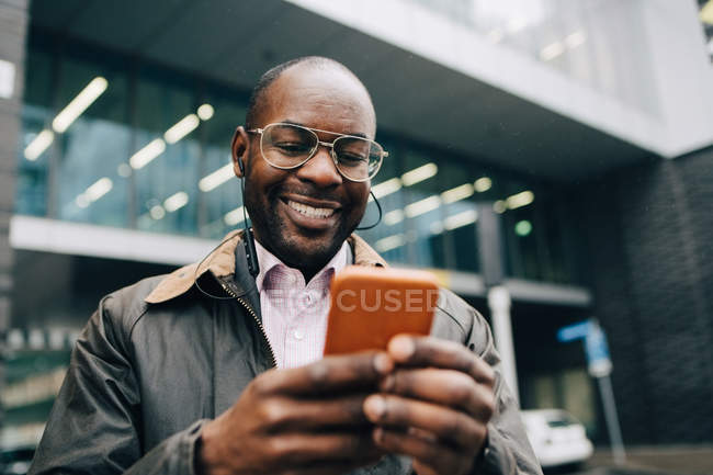 Smiling businessman using smart phone while standing against building in city — Stock Photo