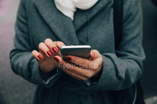 Midsection of businesswoman using smart phone while standing on road in city — Stock Photo