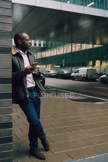 Full length of businessman with mobile phone looking away while standing on sidewalk in city — Stock Photo