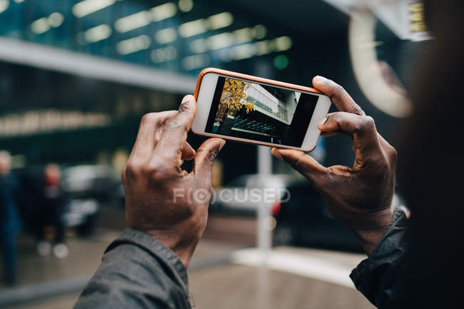 Cropped hands of businessman photographing building with smart phone in city — Stock Photo