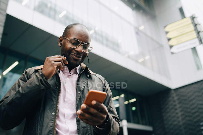 Low angle view of smiling businessman using smart phone while standing against building in city — Stock Photo