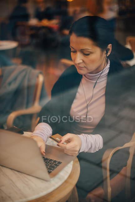Hochwinkelaufnahme der Geschäftsfrau beim Online-Shopping über Laptop, während sie im Café sitzt, durch das Fenster gesehen — Stockfoto