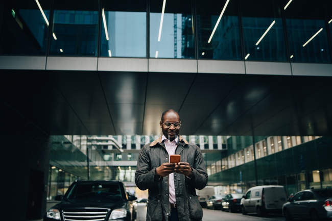 Low angle view of businessman using smart phone while standing on road against building in city — Stock Photo