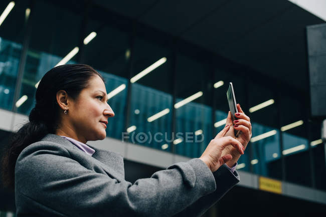 Side view of businesswoman photographing with smart phone while standing against modern building in city — стокове фото