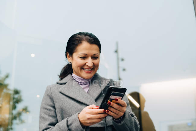 Low angle view of smiling businesswoman using smart phone while standing against building in city — Stock Photo