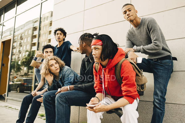 Male friends spending leisure time at sidewalk in city — Stock Photo