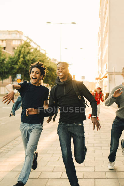 Amici giocosi felici che corrono su strada in città — Foto stock