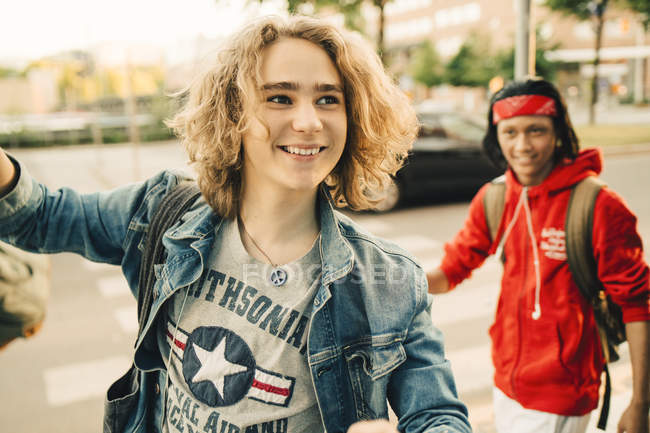 Smiling young man looking away while friend standing in background on street — Stock Photo
