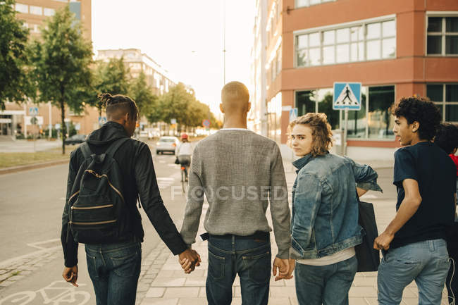 Vista posteriore di amici maschi che camminano fianco a fianco su strada in città — Foto stock