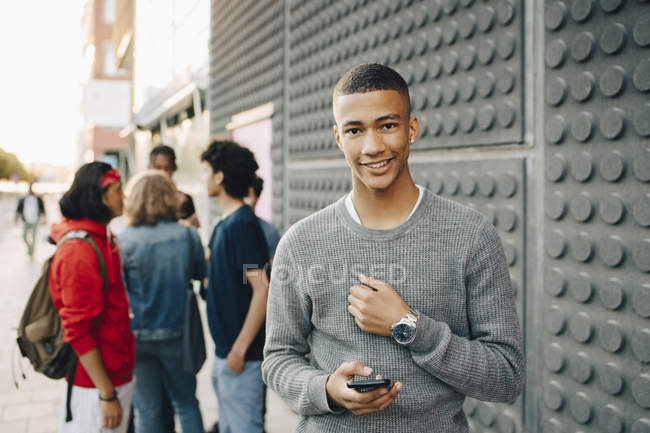 Portrait of smiling teenage boy holding mobile phone while friends standing in background on street — Stock Photo