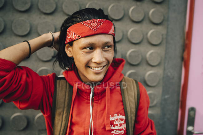 Cheerful young man wearing red bandana while looking away in city — Stock Photo