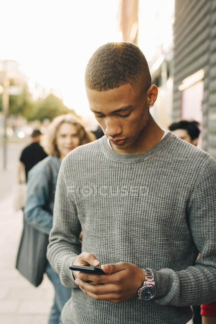 Teenage boy using mobile phone while standing on street in city — Stock Photo